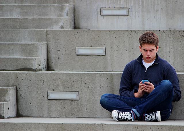 smutný chlapec s mobilem