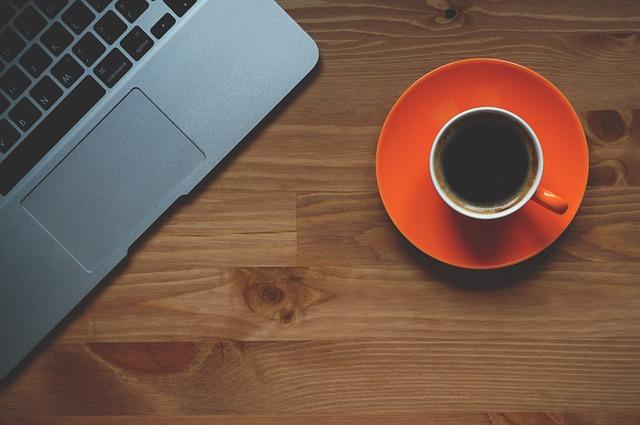 šálek kávy u laptopu
