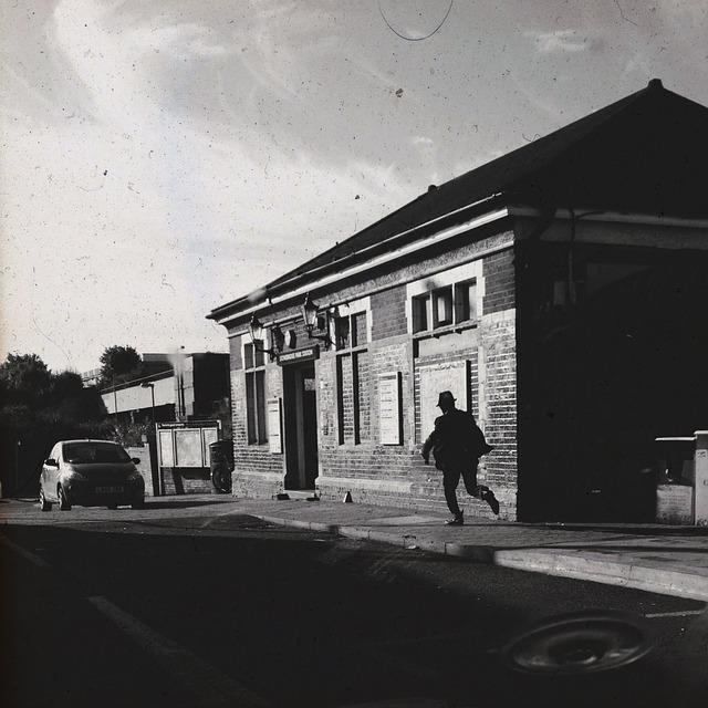 muž běžící po ulici ke dveřím budovy, černobílá fotografie